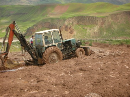 The first tractor begins its futile work, mud sliding back down around it