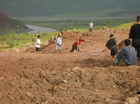 Tajiki citizens labor to shovel mud off the road, since no official help is coming