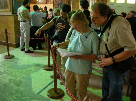 Groups of tourists search for familiar sites in the mosaic, while a baptism is carried out in the background