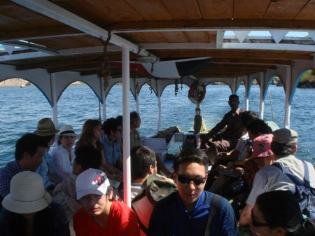 Mahmoud guides the ferry's rudder as our expanded group heads towards the Island