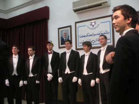 The guys assemble for their first song as the late King Hussein of Jordan watches over them serenely